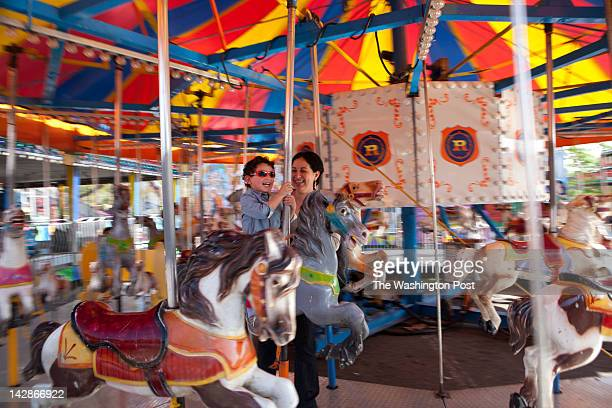 A young rider enjoys the ferris wheel as warm weather welcomed the 2012 opening of Reithoffer Shows' fair at the Landmark Mall in Alexandria Va on...