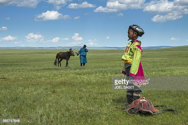 A young rider looks on next to his father and his horse after a horse race during the traditionnal Nadaam festival in a nomad camp in the Ovorkhangai...