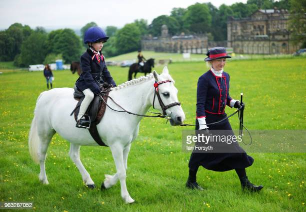 A young rider sits on her horse as her mother leads it to the show field during the Duncombe Park Country Fair on May 28 2018 in Helmsley England Set...