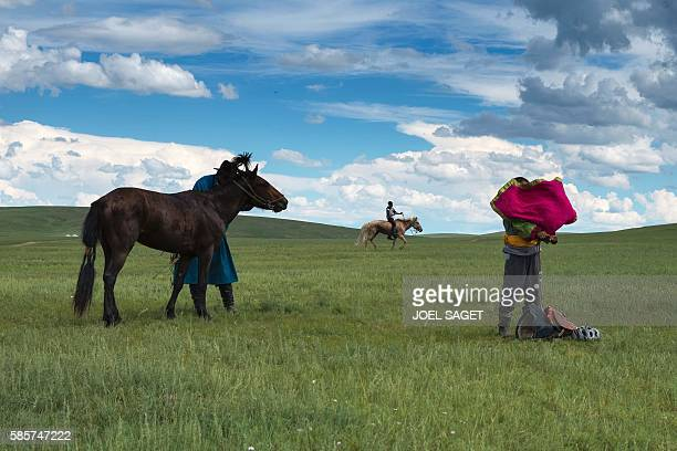 A young rider stand near his father and his horse after a horse race on July 18 2016 during the traditionnal Nadaam festival in the Ovorkhangai...