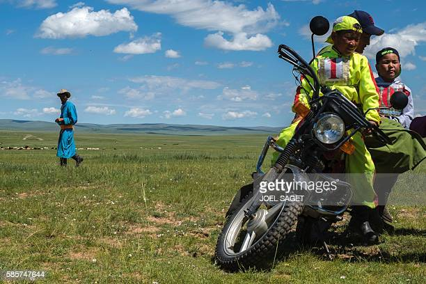 Young riders ride a motorcycle during the traditionnal Nadaam festival in a nomad camp in the Ovorkhangai province on July 18 2016 / AFP / JOEL SAGET