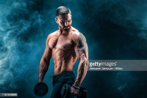 young ripped man bodybuilder with perfect abs, shoulders,biceps, triceps and chest posing - braccio umano foto e immagini stock