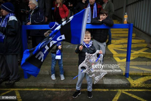 A young Rochdale fan waves his flag whilst holding a tin foil cutout of the FA Cup trophy during The Emirates FA Cup Fifth Round match between...
