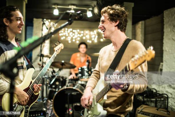 young rock band rehearsing together and laughing - rock music stock pictures, royalty-free photos & images
