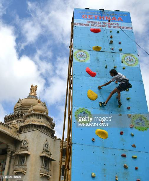 A young rock climber scales a vertical artificial wall in front of the Vidhana Soudha in Bangalore on August 29 to mark the nationwide launch of the...