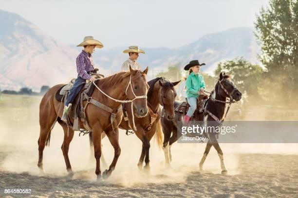 Junge Rodeo Cowboys reiten hintereinander