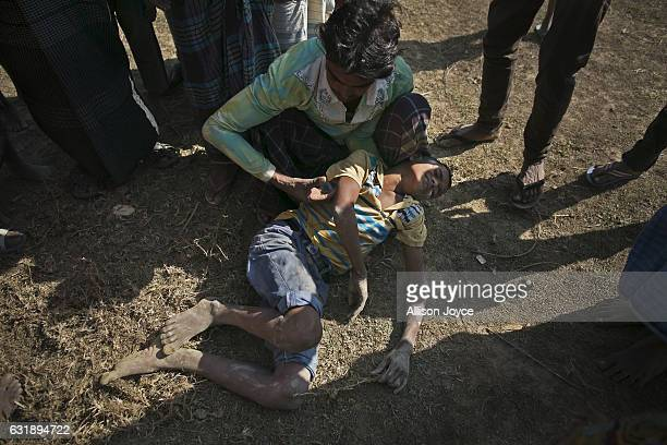 A young Rohingya boy lies injured on the ground after he fell from a high hill as he was building his house in the Balu Kali refugee camp on January...