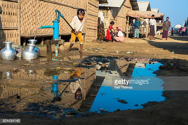 A young Rohingya girl pumps water in a newly constructed shelter area at one of the registered Internally Displaced People's camps on the outskirts...