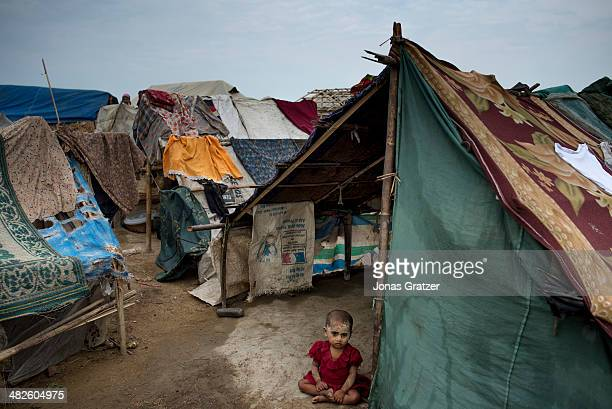 A young Rohingya girl sits outside a tent in one of the largest camps in Sittwe See La Ma Camp Sittwe now has over 125000 people who are isolated...