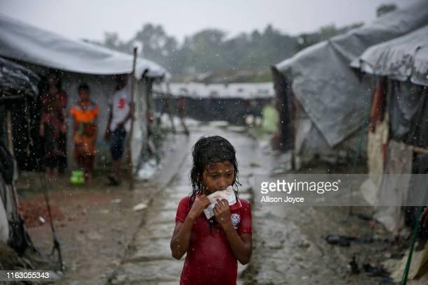 COX'S BAZAR BANGLADESH AUGUST 21 A young Rohingya is seen during a rainstorm at the Nayapara refugee camp on August 21 2019 in Cox's Bazar Bangladesh...