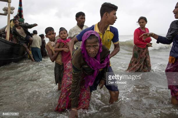 A young Rohingya man carries an elderly woman after the wooden boat they were travelling on from Myanmar crashed into the shore and tipped everyone...