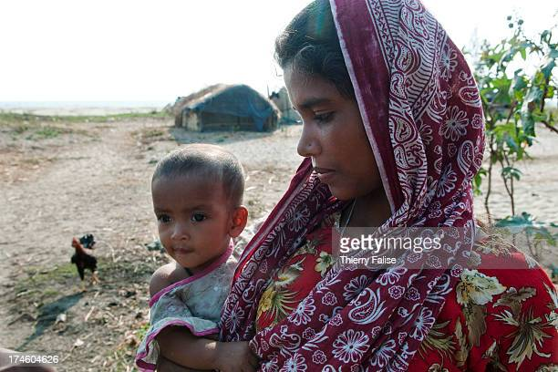 COX'S BAZAR BEACH BANGLADESH A young Rohingya migrant carries her baby near the family hut on a Cox's Bazar area beach The Rohingya is a Muslim...