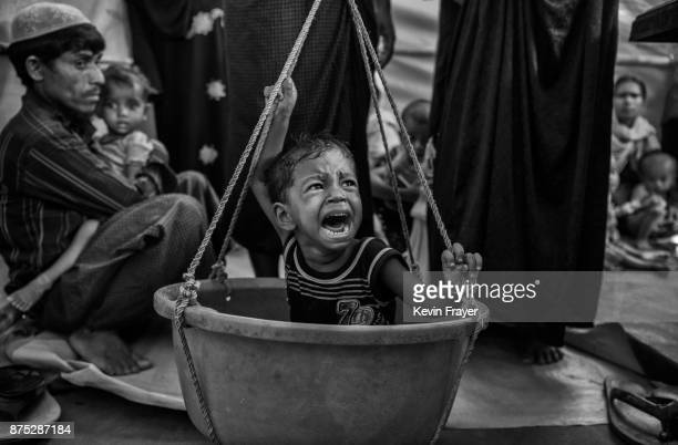 COX'S BAZAR BANGLADESH OCTOBER 25 A young Rohingya Muslim refugee boy suffering from malnutrition is weighed at a field clinic by the NGO Action...