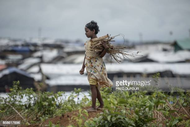 TOPSHOT A young Rohingya Muslim refugee collects wood among graves at Kutupalong refugee Camp in Bangladesh's Ukhia district on October 7 2017 A top...