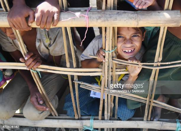 A young Rohingya Muslim refugee looks on through a temporary bamboo barricade at the Thankhali refugee camp in Bangladesh's Ukhia district on...