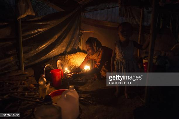 TOPSHOT A young Rohingya Muslim refugee prepares her meal at Balukhali refugee camp in Bangladesh's Ukhia district on October 4 2017 More than 500000...