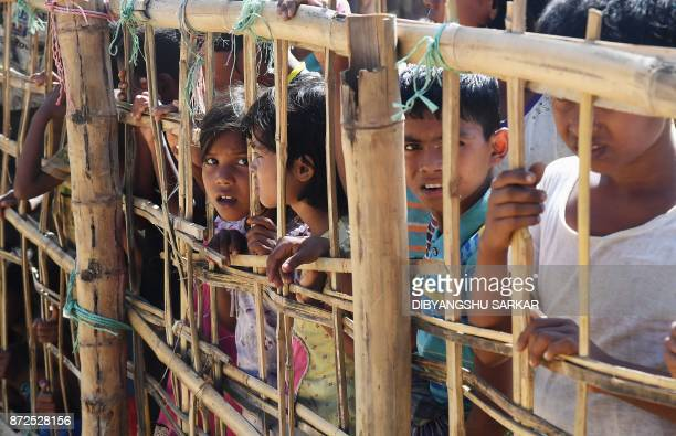 Young Rohingya Muslim refugees look on through a temporary bamboo barricade at the Thankhali refugee camp in Bangladesh's Ukhia district on November...
