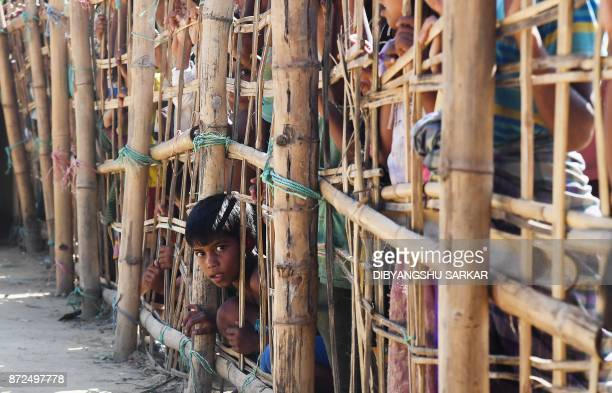 A young Rohingya Muslim refugees looks on through a temporary bamboo barricade at the Thankhali refugee camp in Bangladesh's Ukhia district on...