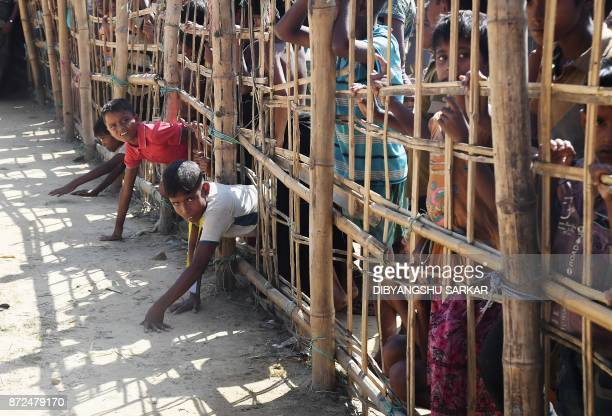 Young Rohingya Muslim refugees pass through a temporary bamboo barricade to collect cooked food at the Thankhali refugee camp in Bangladesh's Ukhia...