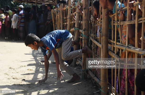 A young Rohingya Muslim refugees passes through a temporary bamboo barricade to collect cooked food at the Thankhali refugee camp in Bangladesh's...