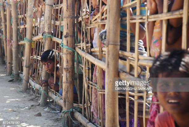 Young Rohingya Muslim refugees reacts as they look through a temporary bamboo barricade to collect cooked food at the Thankhali refugee camp in...