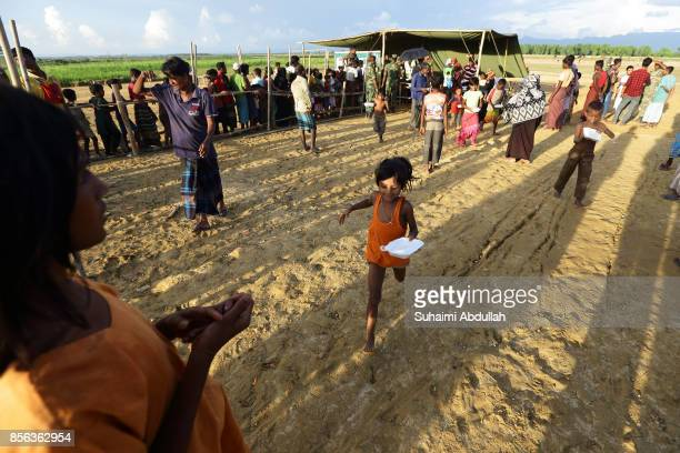 A young Rohingya refugee girl runs after collecting a precooked meal at the distribution point for food centre on September 30 2017 in Teknaf Cox's...