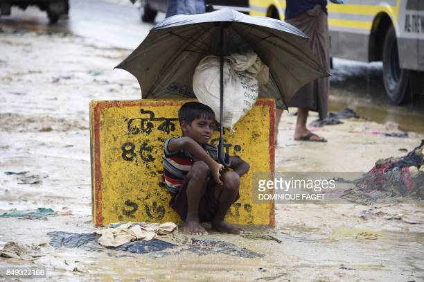 TOPSHOT A young Rohingya refugee shelters from the rain with an umbrella while sitting at Kutupalong refugee camp in the Bangladeshi locality of...
