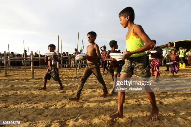 Young Rohingya refugees collect a precooked meal at the distribution point for food centre on September 30 2017 in Teknaf Cox's Bazar Bangladesh Over...