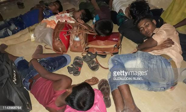 Young Rohingya refugees sleep in a police station before being returned to the camps in Coxs Bazar on May 15 after they were rescued from going on a...