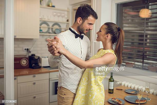 Young romantic couple dancing in the kitchen.