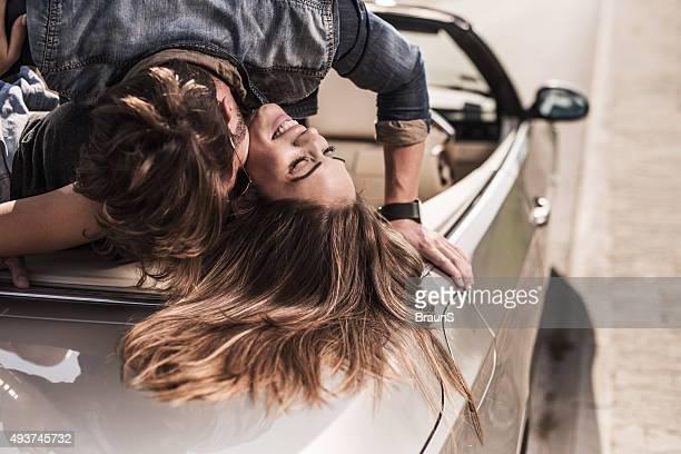 Jovem Casal desfrutar romântico no amor sobre um descapotável.
