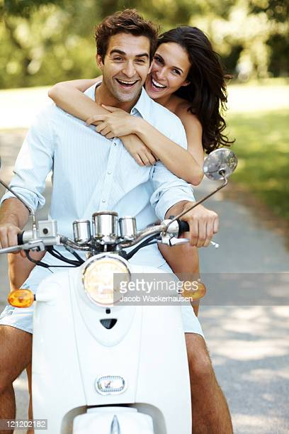 Young romantic couple having fun on a scooter