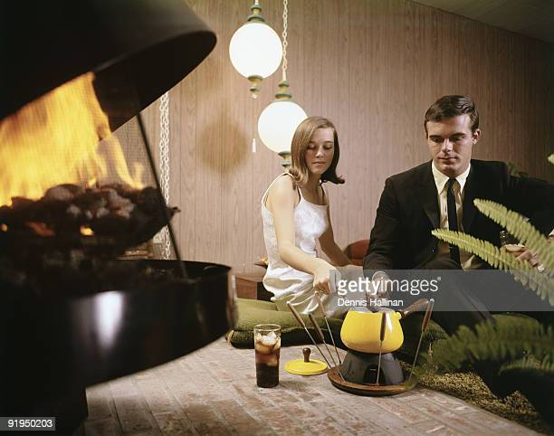 Young romantic couple sitting by fireplace making fond du