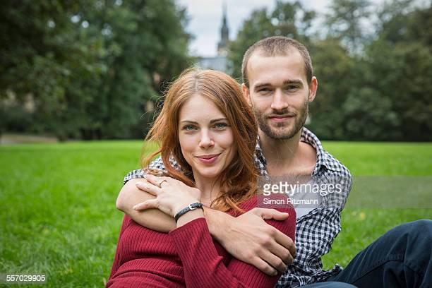Young romantic couple sitting outdoors in grass