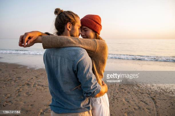 young romantic couple standing face to face at beach against clear sky during sunset - love stock pictures, royalty-free photos & images
