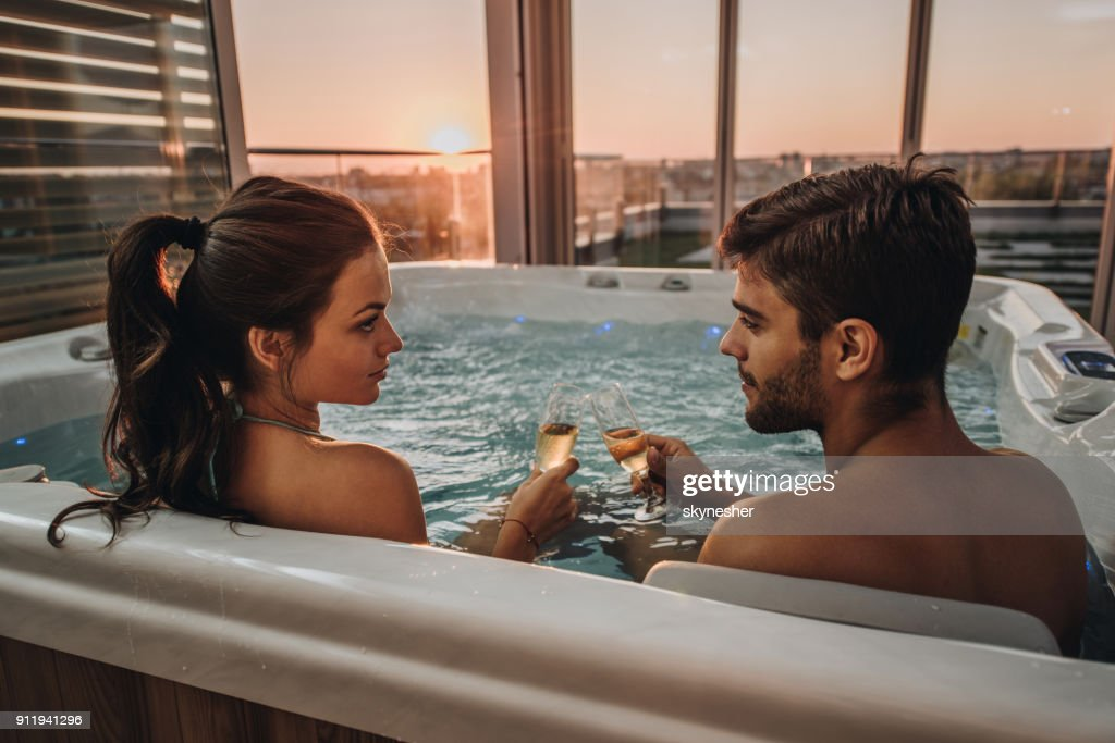 Young Romantic Couple Toasting With Champagne In A Hot Tub ...