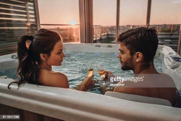 Young romantic couple toasting with champagne in a jacuzzi.