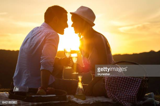 Young romantic couple toasting with wine at sunset.