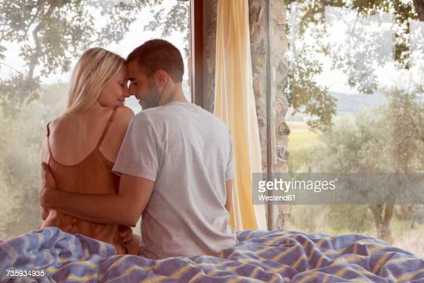 young romantic couple waking up in bed - good morning kiss images stock photos and pictures