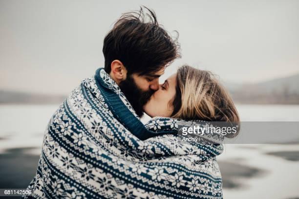jeune homme romantique et femme embrasse tandis que couverts en couverture par une froide journée - hot couple photos et images de collection