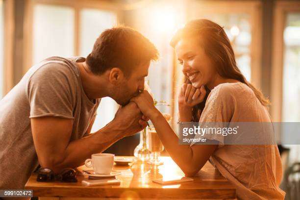 Young romantic man kissing girlfriend's hand in a cafe.