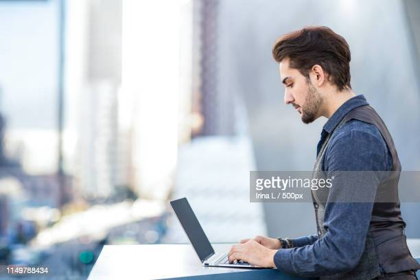young romantic man working on his laptop in the city - 男性用ベスト ストックフォトと画像