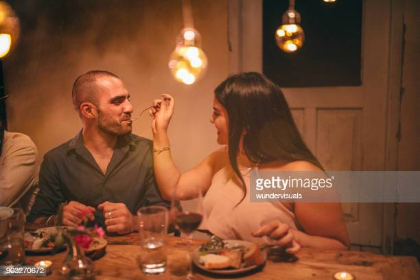 Young romantic woman feeding boyfriend at rustic dinner party