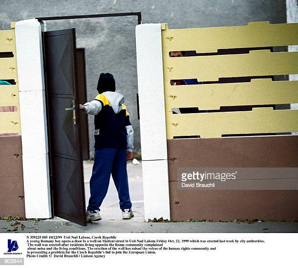 A young Romany boy opens a door in a wall on Maticni street in Usti Nad Labem Friday Oct 22 1999 which was erected last week by city authorities The...