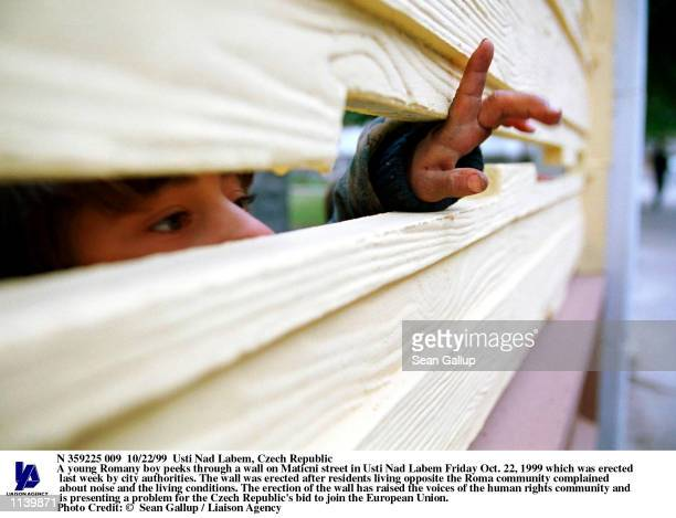 A young Romany boy peeks through a wall on Maticni street in Usti Nad Labem Friday Oct 22 1999 which was erected last week by city authorities The...