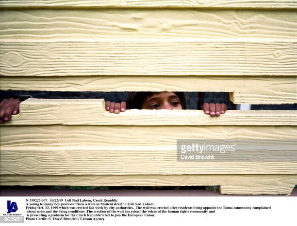 A young Romany boy peers out from a wall on Maticni street in Usti Nad Labem Friday Oct 22 1999 which was erected last week by city authorities The...