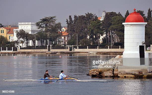 A young rower team trains next to the main lighthouse in southern Croatian Adriatic town of Zadar on January 25 2010 AFP PHOTO/ HRVOJE POLAN