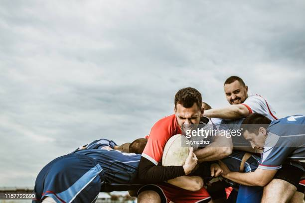 young rugby player trying to pass through his rivals on a match. - scrum stock pictures, royalty-free photos & images