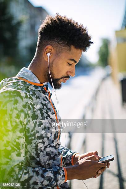 Young runner listening music on mobile phone