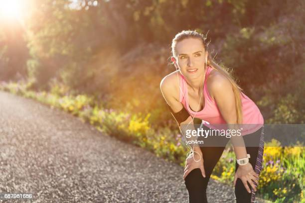 young runner relaxing & smiling during exercise - hand on knee stock pictures, royalty-free photos & images